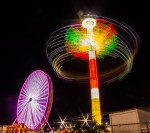long exposure photograph of Ferris wheel and carnival swing at night